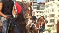 Palestinians ride horses as they hold flags during a demonstration organized by Palestine Equestrian Federation to show solidarity with Jerusalem and...