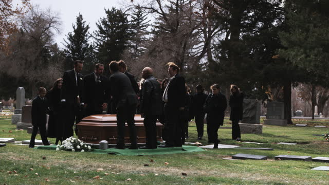 pallbearers carrying coffin to a gravesite