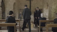 Pallbearers leaving Church with coffin followed by family