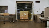 WS Pallet of stacked boxes being pulled through doorway by factory worker/ Door closing/ New Jersey