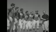 members of Stanford University's football team the Cardinals stand in V formation and wave at camera prior to practice session / CU coach Clark...