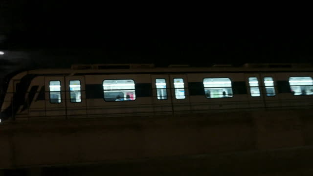 A pan across a fast moving train of the rapid metro in Gurgaon, Haryana, India