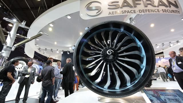 MS pan across a Safran Leap jet engine on display at the Safran SA pavilion WS high angle view of visitors walking past engine displays WS visitors...