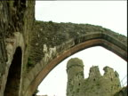 Pan across arch within Conwy Castle grounds another section of Castle in background