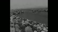 Pan across crowd in stands at Agua Caliente Racetrack / pan across female jockeys standing in line posing for photo opportunity / race horses parade...