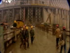 Pan across from workers on road to water gushing through Three Gorges Dam in Yangtze River Yichang Hubei Province