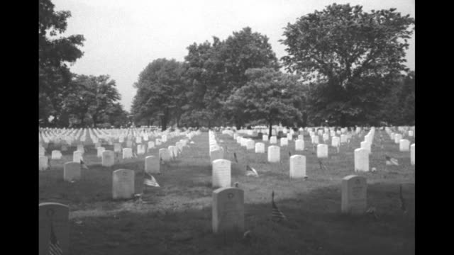 Pan across graves American flags flying next to headstones trees in bg / rows of headstones / round building by road in cemetery rows of headstones...