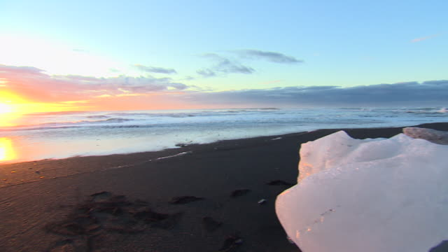 Pan across icebergs sitting incongruously on a beach in Iceland at sunset.