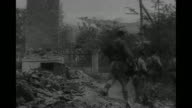 Pan across Novorossiysk / VS Soviet soldiers and marines entering city / soldiers look at wrecked building / soldier looking down at wreckage removes...