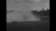 Pan across road and forest filled with smoke / smoke floating from bank of river onto river / soldiers dragging boats down slope towards water /...
