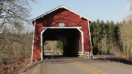 Pan across road to red covered bridge in rural setting.
