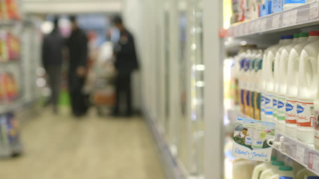 Pan across to a refrigerator full of milk in a supermarket.