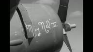 Pan across US planes parked on airfield / members of ground crew sitting on wings of plane loading ammunition into guns / CU words 'My Nel II'...