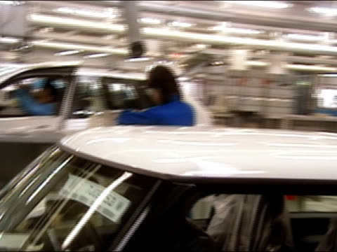 Pan along factory workers working on Minis and BMWs on assembly lines at BMW plant in Tokyo, Japan