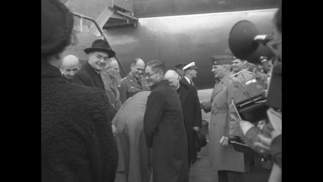 VS Pan Am Boeing 377 Stratocruiser taxis to a stop men in foreground / Cardinal Francis Spellman archbishop of New York walks down plane stairs / CU...