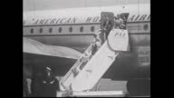 Pan American World Airlines plane taxies / passengers down stairs see Polar Route sign on plane