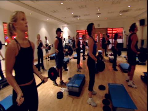 Pan around body pump aerobics class people lifting barbells