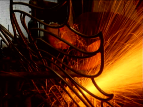Pan around welder wearing safety goggles as sparks spray in all directions