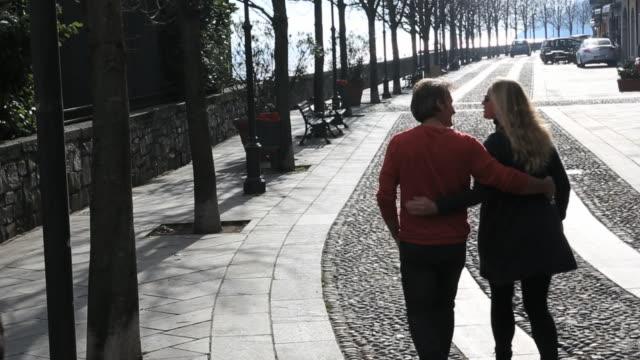 Pan as couple walk along cobblestone street, lakeside village