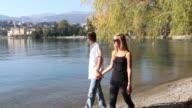 Pan as couple walks along lake edge, town behind