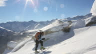 Pan as ski mountaineer ascends snow slope, on windy day