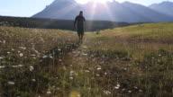 Pan as teen boy walks thru meadow of flowers, on cell phone