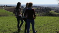 Pan as teen  girls walk across green field to viewpoint