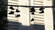 Pan camera captures hanging shoes on electric wire at Brooklyn. Background is bridge pier of Manhattan Bridge.