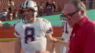 1985 MS pan coach directing LA Express football player Steve Young onto field at beginning of game against Tampa Bay Bandits/ WS Young running on to field/ USA