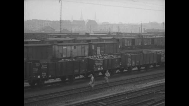 Pan WS coal barges waiting for transport / WS mounds of coal / pan WS train cars full of coal / pan WS quiet railroad terminal at Duisburg station...