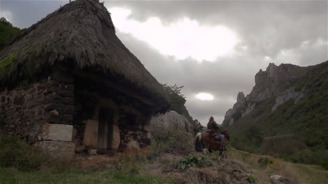 W/S pan cowboy (rider) moving away from an old mountain cabin w/ straw roof (teito)