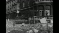 Pan damage done to Buckingham Palace by a German bomb during World War II / British Prime Minister Winston Churchill walks briskly in street /...