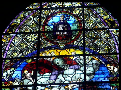 Pan down beautifully coloured stain glass window depicting the scene of the nativity Seville Cathedral.