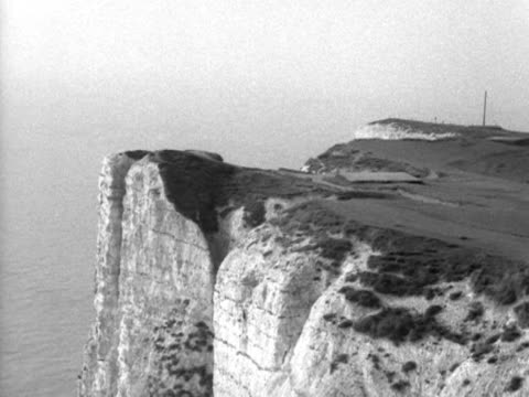 Pan down from a cliff top at Beachy Head to a lighthouse