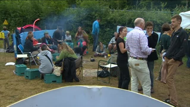 Pan down from antifracking protest camp to 'No Fracking' placard