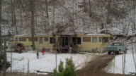 pan down from bare branches of trees to double wide trailer house in woods. snow covers ground, children play in yard, and pickup truck parked in driveway. lower class.