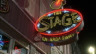 pan down from neon sign for the stage on broadway. bar or nightclub.