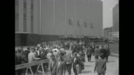 Pan down of the exterior of the Coliseum with a long line of people below / MS the line of people at street level / MS Gov Averell Harriman Robert...