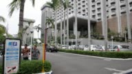 Pan down on Sari Pan Pacific Hotel car driving towards hotel exit security guard walking past in Jakarta Indonesia on Friday Jan 15 Pan of taxi...
