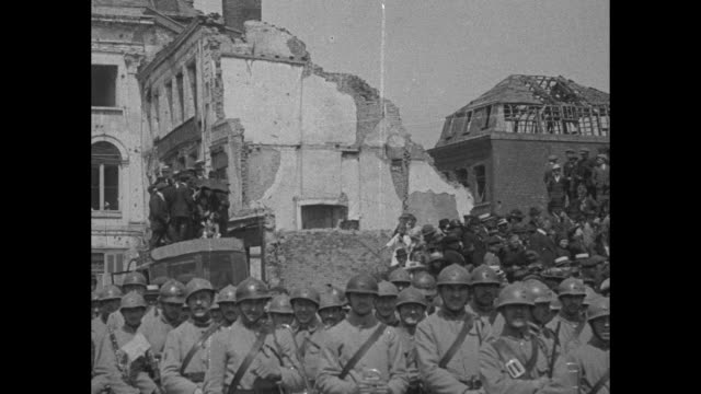 Pan down ruins podium next to it with French flags on top crowd in foreground / Marshal Ferdinand Jean Marie Foch walks with group of VIPs past...