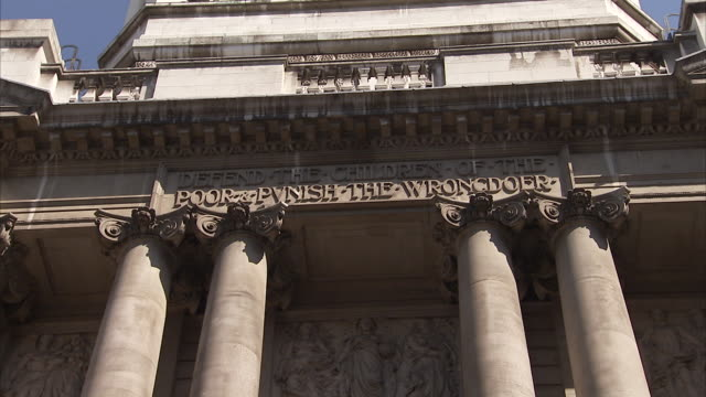 Pan down the exterior of the Old Bailey court to the statues situated above the entranceway. Available in HD.