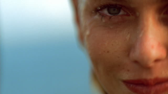 Pan extreme close up blonde woman with wet face / water splashing on face / smiling and laughing