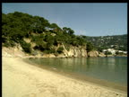 Pan from low rocky cliffs and empty beach to a calm inlet. Costa Brava Spain.