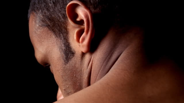 Pan from man's upper back to profile of head