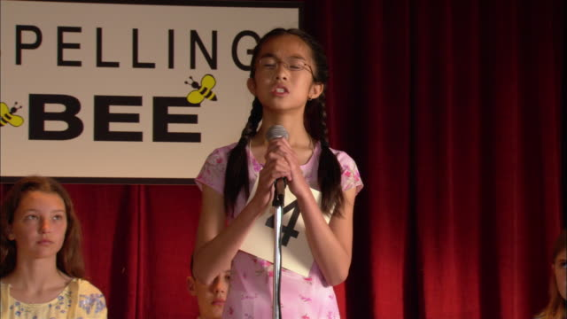 Pan from moderator announcing word at spelling bee to girl spelling word at microphone / Los Angeles, California