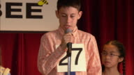 Pan from moderator of spelling bee announcing word at podium to nervous boy spelling word at microphone on stage / spelling word correctly and celebrating / Los Angeles, California
