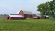 Pan from red barns to farm house