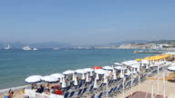 Pan from right to left from the promenade across the beach with whiteblue parasols and beach chairs at the Croisette in Cannes on the French Riviera...