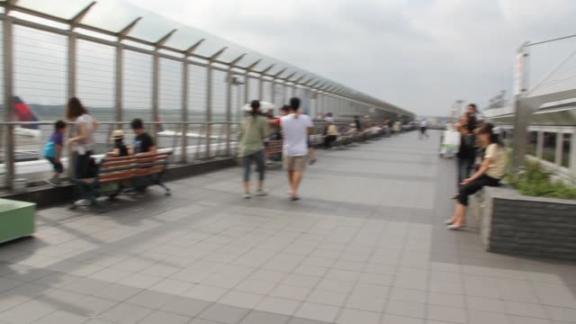 Pan from sign 'Narita Airport Terminal' to observation deck with men women children