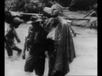 Pan group of Australian soldiers clean weapons smile while in New Guinea during World War II / soldier helps injured comrade whose eyes are bandaged...